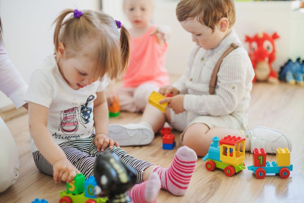 niños pequeños jugando en el suelo con un trenecito de madera