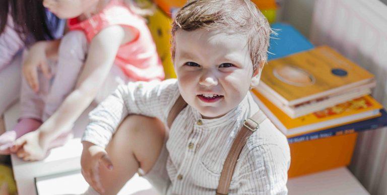 Niño en guardería sonríe a la cámara